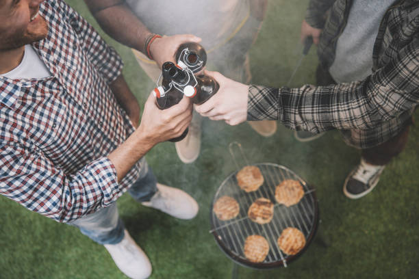 top view of young friends drinking beer and making barbecue stock photo