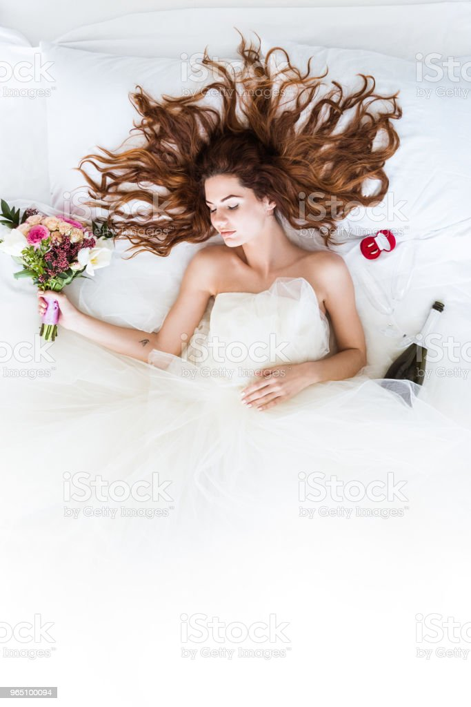 Top view of young girl in wedding dress sleeping in bed with flowers and wedding rings zbiór zdjęć royalty-free