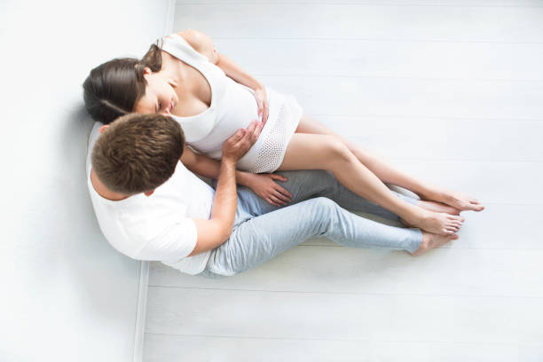 Top view of young man and pretty pregnant woman stock photo