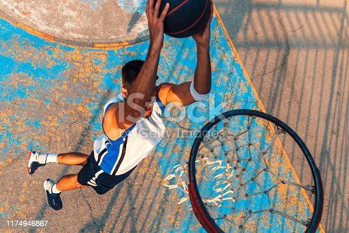 Top view of young man playing basketball outdoor. Slam dunk.