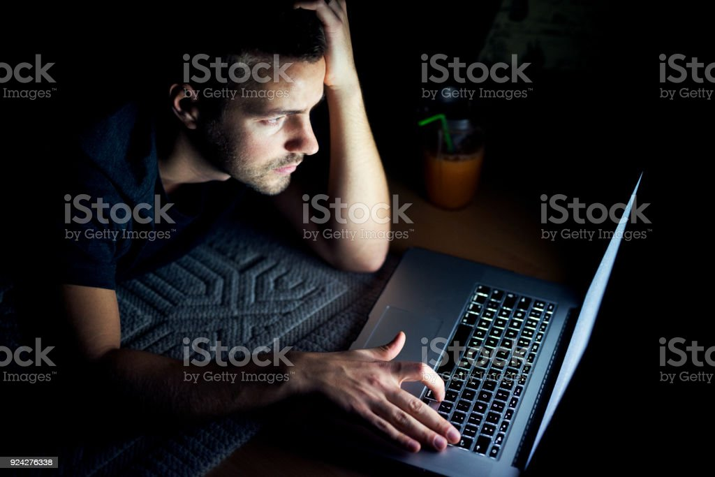 Top view of young man reading news on laptop stock photo