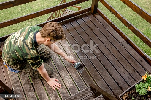 istock Top view of young man staining garden terrace wooden boards outdoors in spring. Terrace wood stain concept. 1154086261