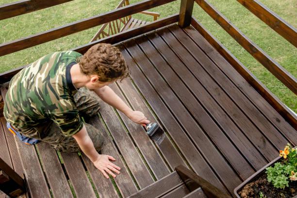 bovenaanzicht van jonge man kleuring tuinterras houten planken buiten in het voorjaar. terras hout vlek concept. - houtbeits stockfoto's en -beelden