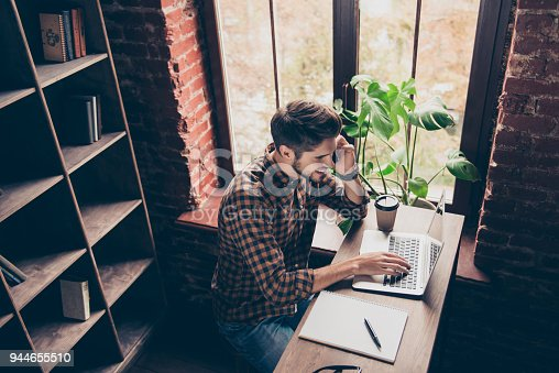 istock Top view of young student working on laptop and talking on phone 944655510
