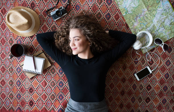 A top view of young teenage girl planning a holiday at home. stock photo