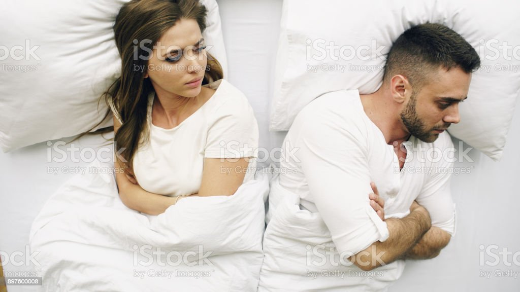 Top view of young upset couple lying in bed have problems after quarrel and angry each other at home stock photo