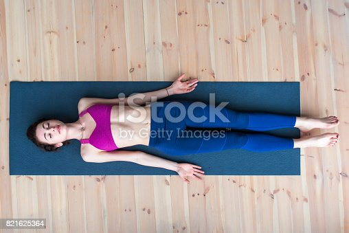 istock Top view of young woman lying in corpse or dead body pose relaxing after practicing yoga 821625364