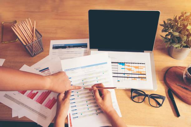 draufsicht der junge berufstätige frau mit laptop und lesung jährlichen bericht-dokument bei der arbeit. verkauf-bericht auf notebook anzeigen. - lesen arbeitsblätter stock-fotos und bilder