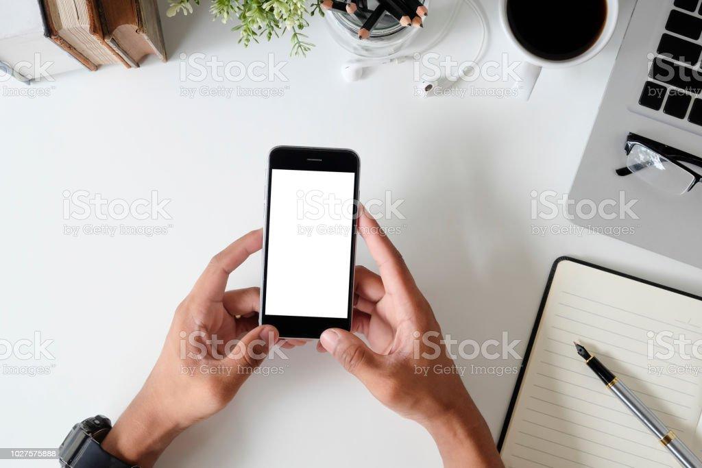 Vue de dessus bureau bureau avec maquette smartphone sur les mains avec un écran vide. photo libre de droits