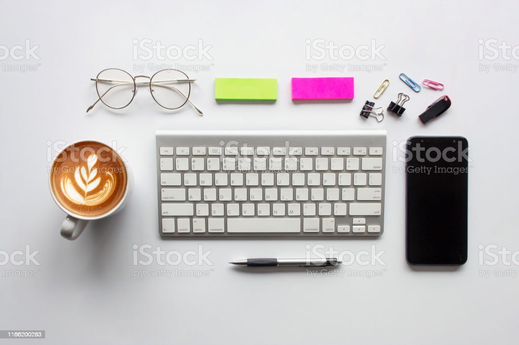top view office table desk. coffee cup, smartphone, pen, keyboard and...