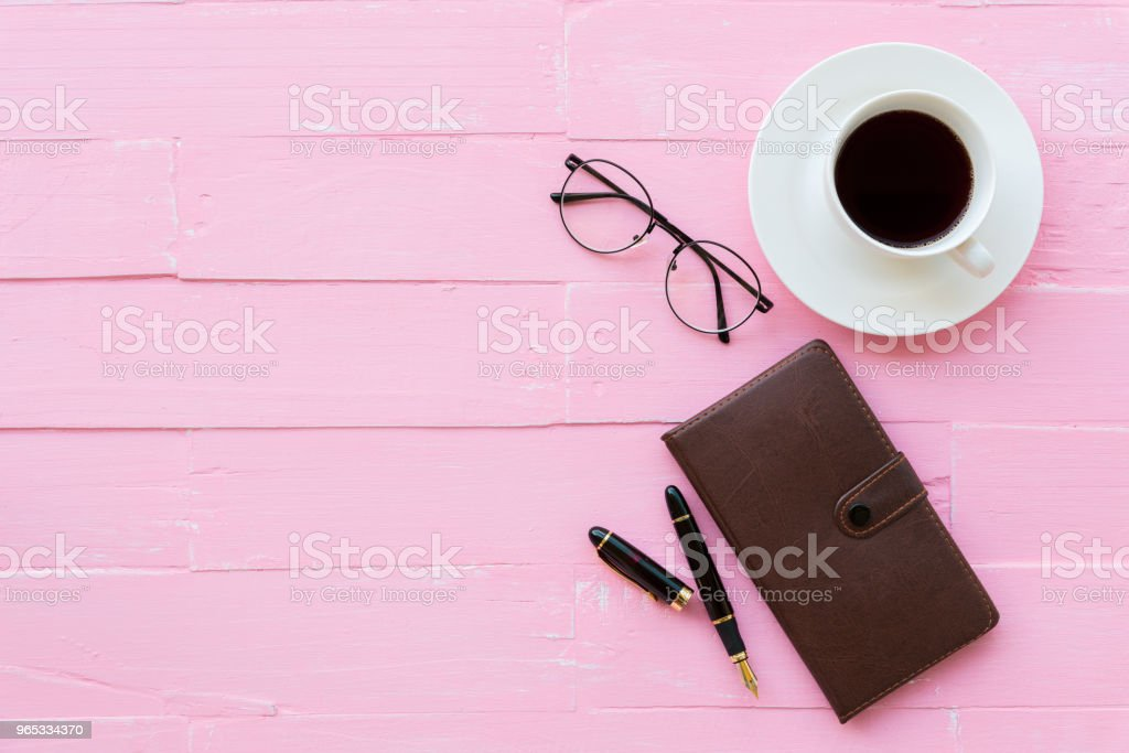 Top view office table with workspace and office accessories including glasses, black pen, notebook and coffee cup on pink wooden background. zbiór zdjęć royalty-free