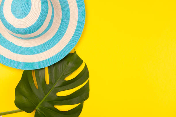 Top view on beach accessories on yellow background - striped blue hat and monstera leaf. Concept of the long-awaited vacation at sea and travel. Advertising space stock photo