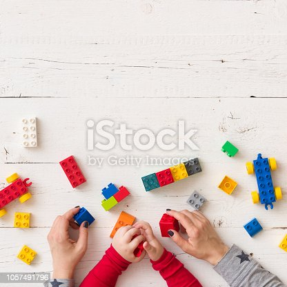 istock Top view on child's and mother's hands playing with colorful plastic bricks, toys and building from them. Learning by playing. 1057491796