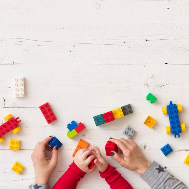 bovenaanzicht op kind en moeder's handen spelen met kleurrijke kunststof bakstenen, speelgoed en ander gebouw van hen. leren door te spelen. - background baby stockfoto's en -beelden
