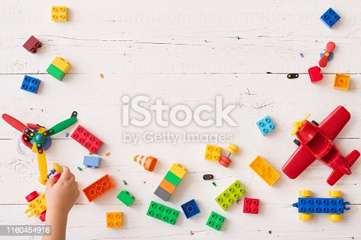 Top view on child's hand playing with multi-color plastic bricks at the table. Toddler having fun and building out of bright constructor bricks. Early learning. Developing toys