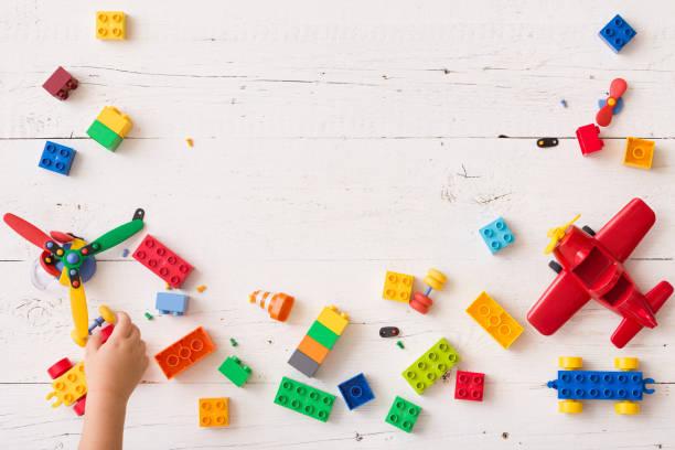 兒童手在桌子上玩多色塑膠磚的頂視圖。幼兒有樂趣和建設明亮的建設者磚。早期學習。開發玩具 - 玩具 個照片及圖片檔