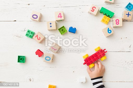 istock Top view on child's hand playing with wooden cubes with numbers and colorful toy bricks on white wooden background. Baby with toys 1007451378