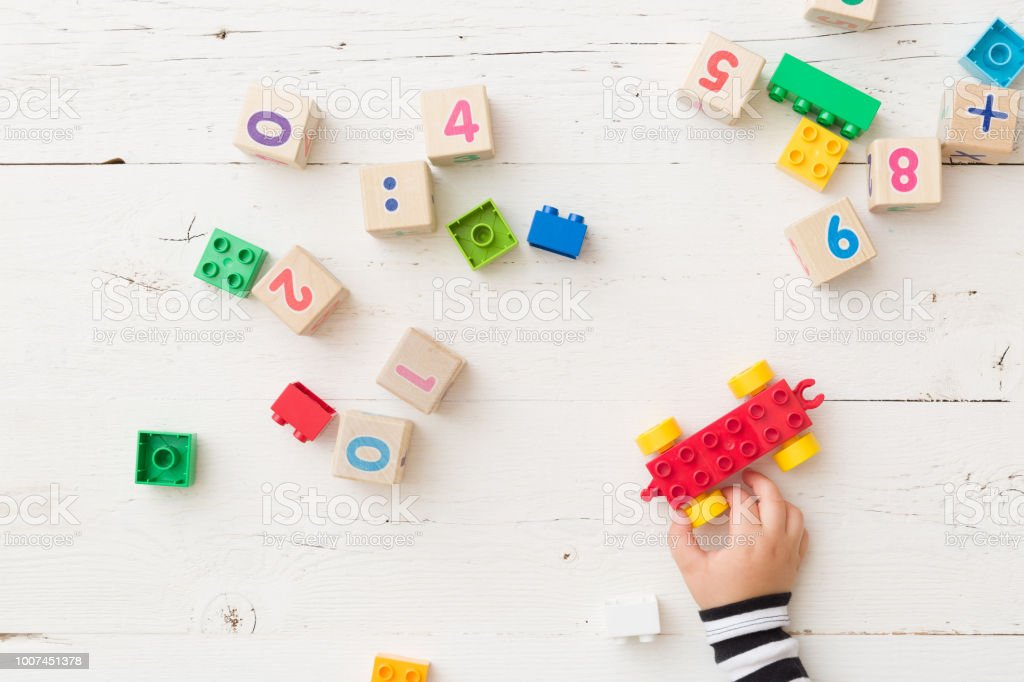 Top view on child's hand playing with wooden cubes with numbers and colorful toy bricks on white wooden background. Baby with toys stock photo