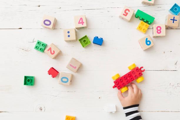 bovenaanzicht op kind hand spelen met houten blokjes met getallen en kleurrijk speelgoed bakstenen op witte houten achtergrond. baby met speelgoed - background baby stockfoto's en -beelden