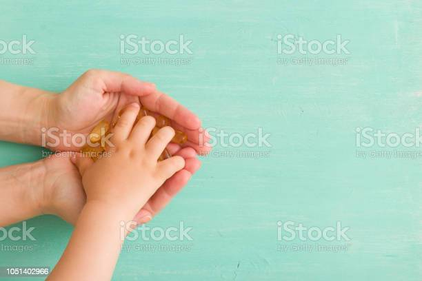 Top view on childs hand taking capsules omega 3 from mothers hands on picture id1051402966?b=1&k=6&m=1051402966&s=612x612&h=0bcwrvnvttefila4n5f2f9jnqzfrumuptlbmr54e9e0=