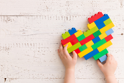 istock Top  view  on child's hands playing with bright heart made of  colorful plastic bricks on old wooden table. Creative building out of bright constructor bricks. Early learning. Developing toys 1051405702