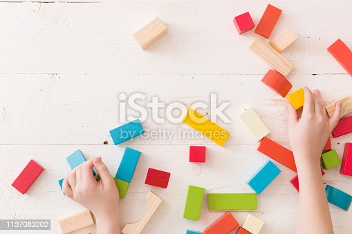 657779378 istock photo Top view on child's hands playing with color wooden cubes and details 1137083202