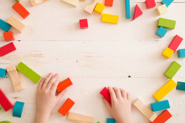 Top view on childs hands playing with colorful wooden bricks on the picture id1017872588?b=1&k=6&m=1017872588&s=612x612&w=0&h=ockvv6bddzlszhfex gya 7dodlkzwbsm  pvxpey9a=