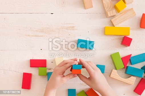657779378 istock photo Top view on child's hands playing with colorful wooden bricks on the white table background.. Kid building with geometric shapes. Learning and education concept. 1018736226