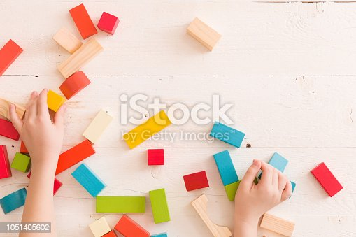 657779378 istock photo Top view on child's hands playing with colorful wooden bricks on the white table background.Kid building with geometric shapes. Learning and education concept. 1051405602