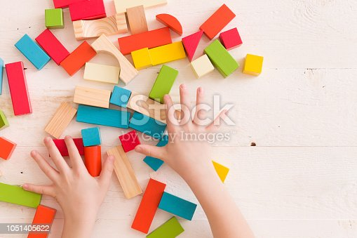 657779378 istock photo Top view on child's hands playing with colorful wooden bricks on the white table background..Kid building with geometric shapes. Learning and education concept. 1051405622