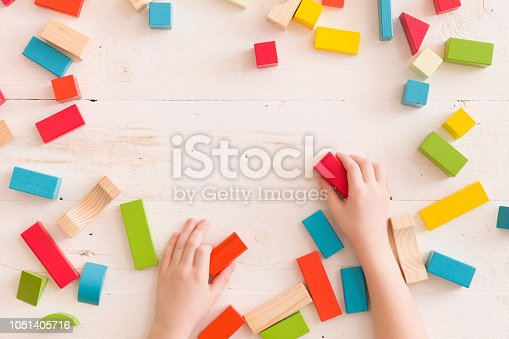 657779378 istock photo Top view on child's hands playing with colorful wooden bricks on the white table background.Kid building with geometric shapes. Learning and education concept. 1051405716