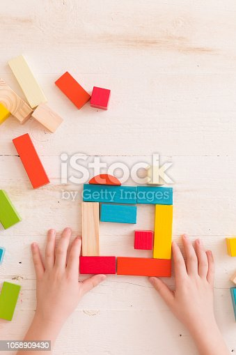 657779378 istock photo Top view on child's hands playing with colorful wooden bricks on the white table background.Kid building with geometric shapes. Learning and education concept. 1058909430