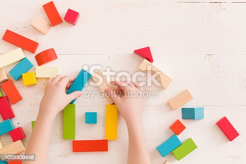 657779378 istock photo Top view on child's hands playing with colorful wooden bricks on the white table background.Kid building with geometric shapes. Learning and education concept. 1058909448