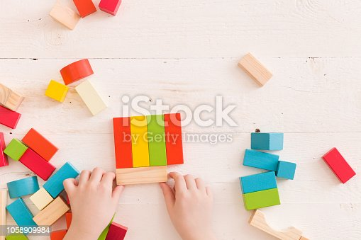 657779378 istock photo Top view on child's hands playing with colorful wooden bricks on the white table background.Kid building with geometric shapes. Learning and education concept. 1058909984
