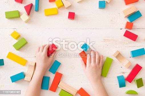 657779378 istock photo Top view on child's hands playing with colorful wooden bricks on the white table background. Learning and education concept. 1137083192