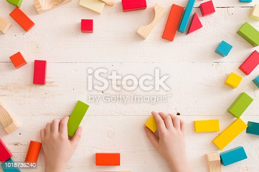 657779378 istock photo Top view on child's hands playing with colorful wooden bricks on white table background. Boy building with wooden constructor. Education concept 1018736240