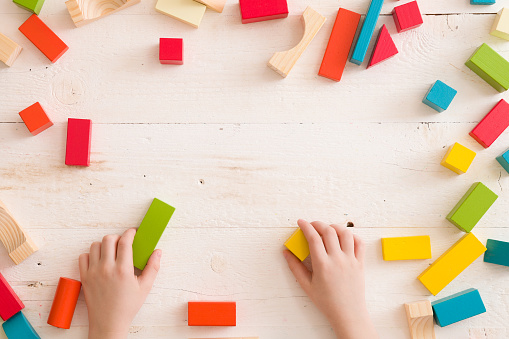 istock Top view on child's hands playing with colorful wooden bricks on white table background. Boy building with wooden constructor. Education concept 1018736240