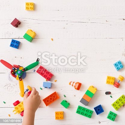 istock Top view on child's hands playing with toys, wooden cubes with numbers and plastic bricks on white wooden table background 1057491690