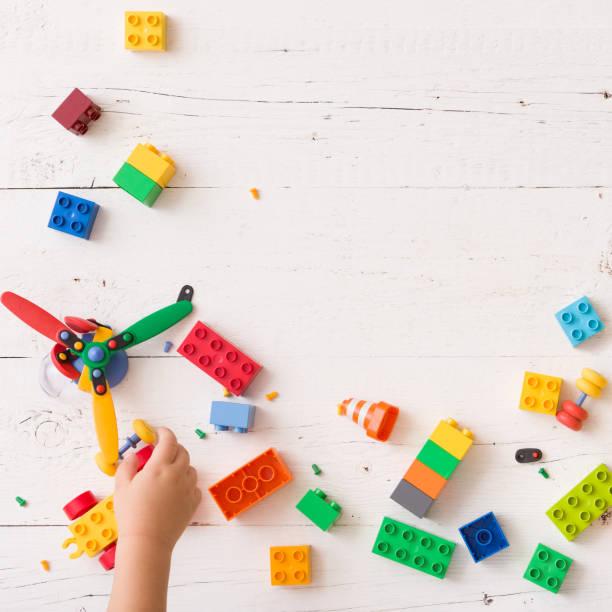 draufsicht auf die hände des kindes spielen mit spielzeug, hölzerne würfel mit zahlen und plastikziegelsteine auf weißer holztisch hintergrund - wachstumstabelle baby stock-fotos und bilder