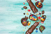 Top view on chocolate traditional easter eggs and bunnies with bright colorful dragee and sugar sprinkles or confetti on wooden background?with copy space