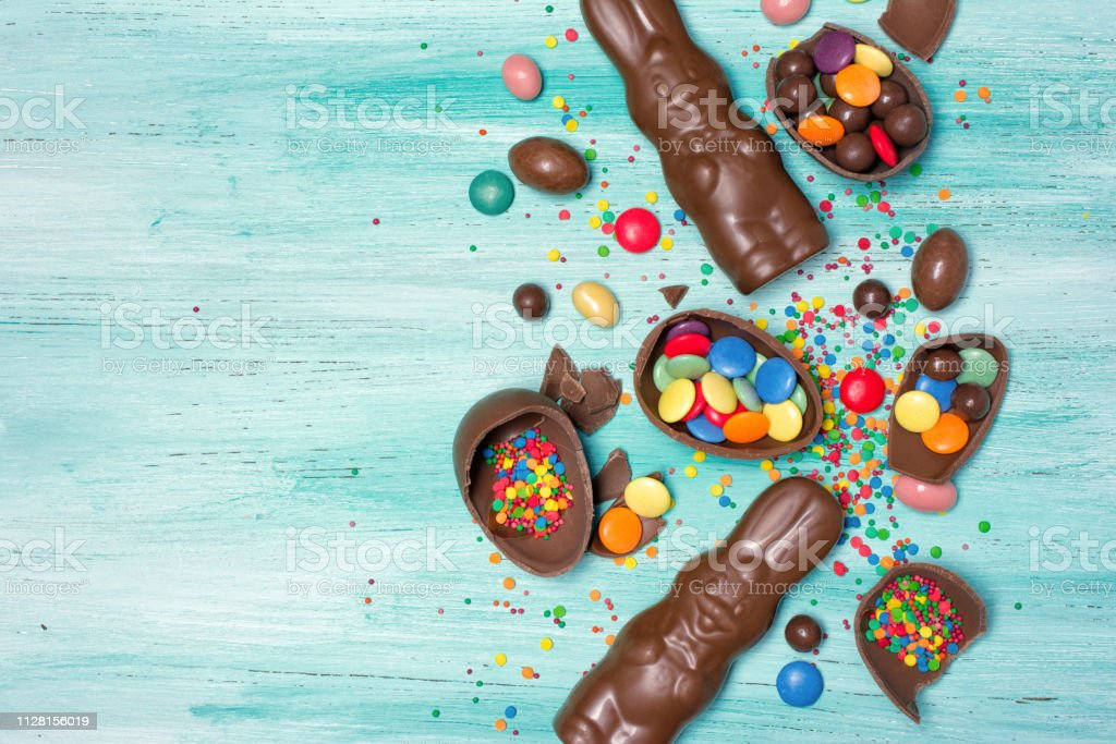 Top view on chocolate traditional easter eggs and bunnies with bright colorful dragee and sugar sprinkles stock photo