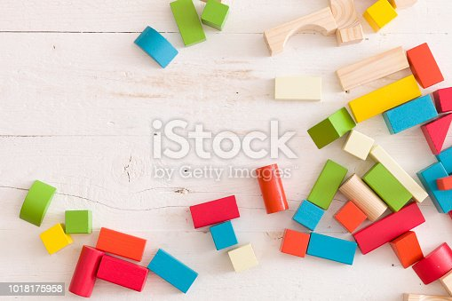 657779378 istock photo Top view on colorful wooden bricks on the white table background. building with geometric shapes. Learning and education concept. 1018175958