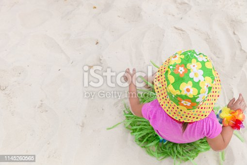 Top view on cute little toddler girl in Hawaiian outfit sitting on the sand on a sunny day. Summer concept.
