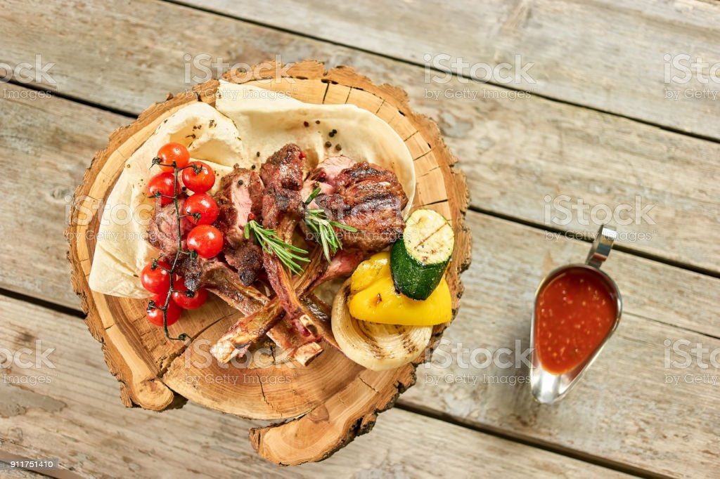 Top view on dish with roasted lamb ribs with tomatoes and sauce. stock photo