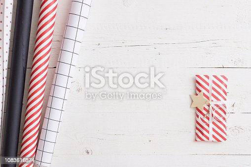 istock Top view on gift being wrapped in Christmas or birthday paper. Paper and decorations on old white wooden table or background. Preparations for celebration or party. Holiday season 1083616874