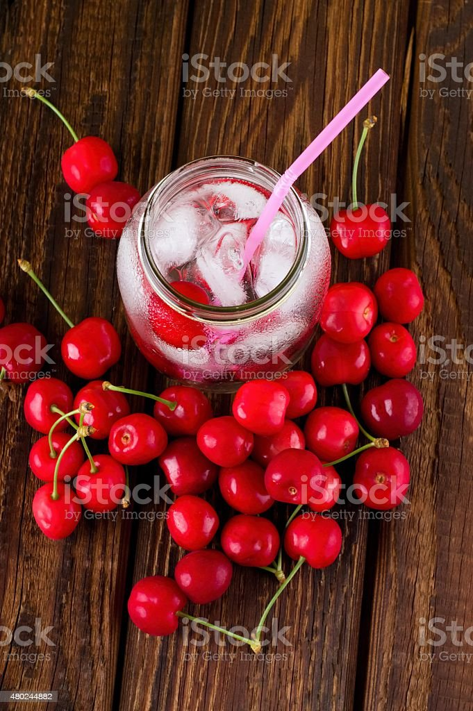 Top view on ice cubes in jar and cherries around stock photo