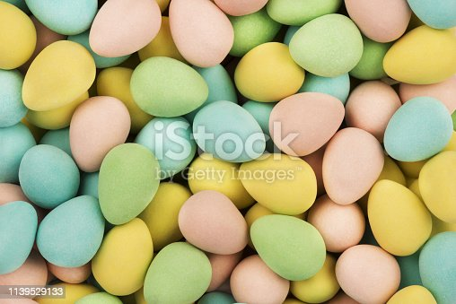 Top view on mini chocolate easter eggs candies as a background. Copy space for your text.
