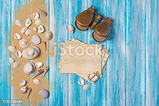 istock Top view on mock-up of vintage photo cards and binoculars with seashells 1131735144