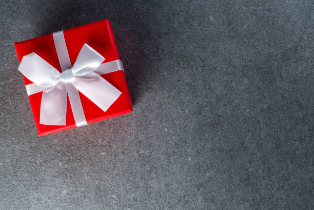 Top view on nice Christmas gift wrapped in red gift paper with white bow on dark background. New Year, holidays and celebration concept stock photo