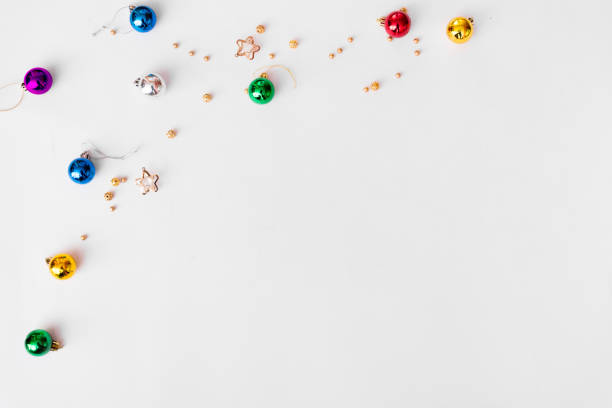 Top view on nice Christmas gift wrapped in white gift paper, Christmas tree decorations on white wooden background with sparkling stars. New Year, hol stock photo
